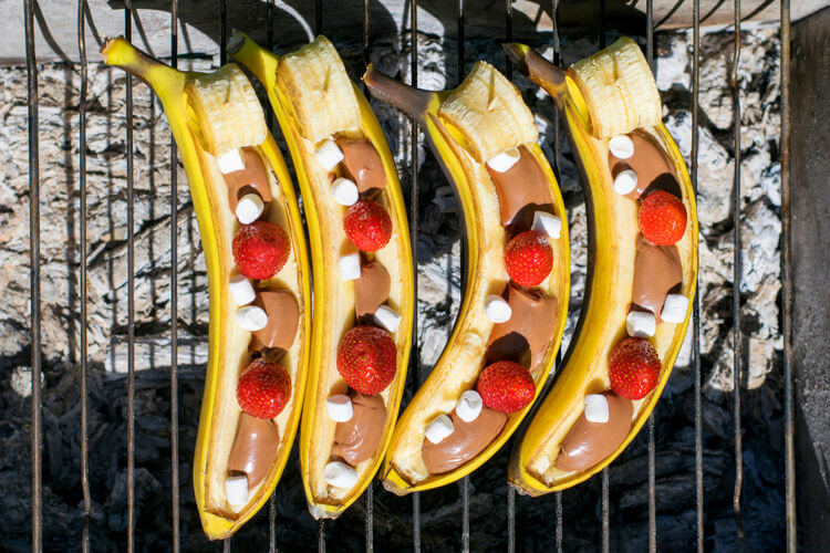 Banana boats cooking on a grill with chocolate and marshmallow