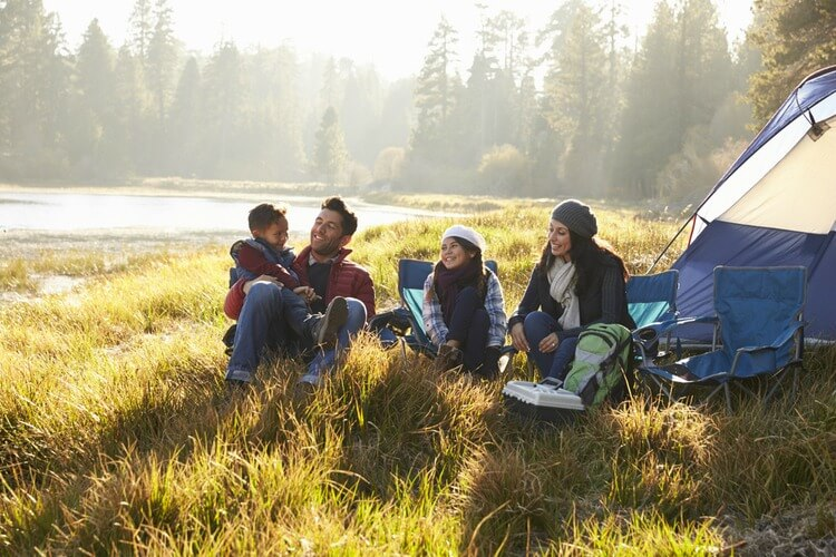 Family camping by lake wearing hats, coats and scarves