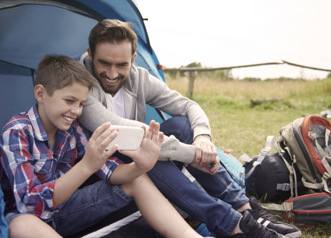 Dad and son using phone on a camping trip