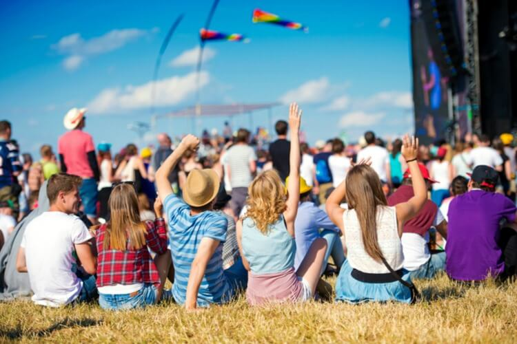 Young people sitting on a field enjoying an outdoor festival