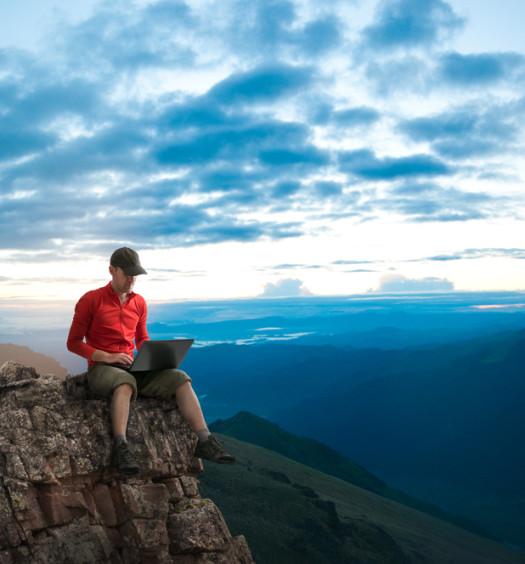 Man blogging outdoors