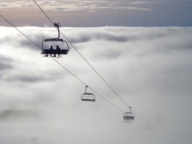 Skiers on ski lift up in the clouds