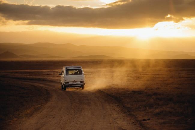 Van driving down dusty road
