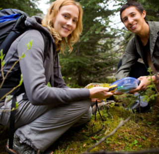 Two people geocaching in a forest