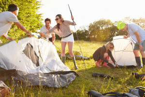 Friends pitching a tent on a camping holiday