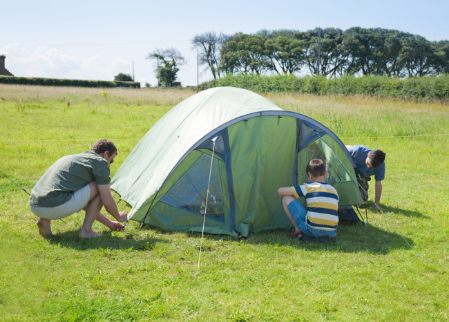 Family putting up a tent in a field