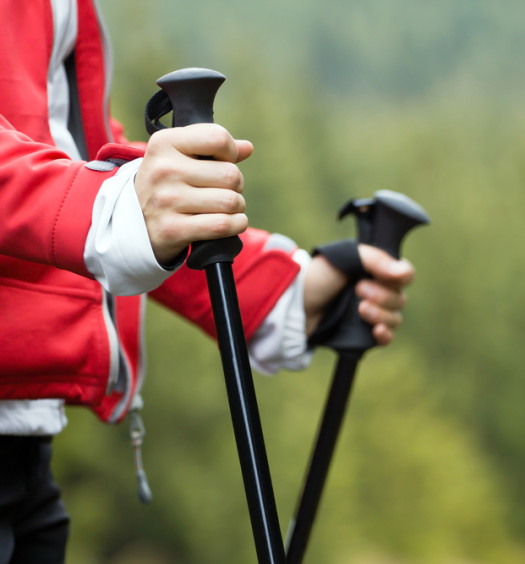 Woman nordic walking using walking poles