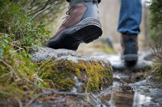 Man walking across a stream wearing walking boots