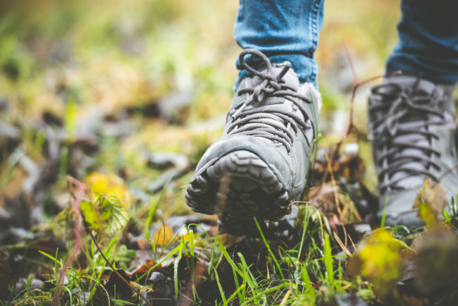 woman walking through a muddy field wearing hiking boots