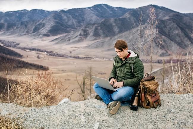 man blogging outdoors on his laptop