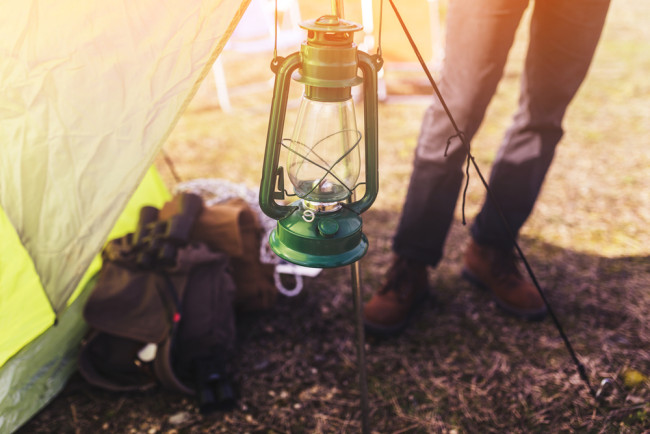 Woman camping standing next to lantern and tent