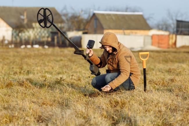 Man metal detecting in a field