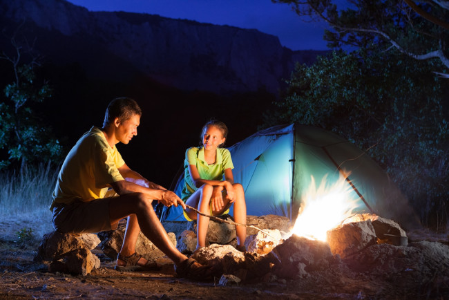 Couple camping around a campfire at night