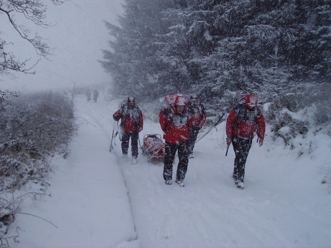 Mountain rescue rescuing someone in the snow