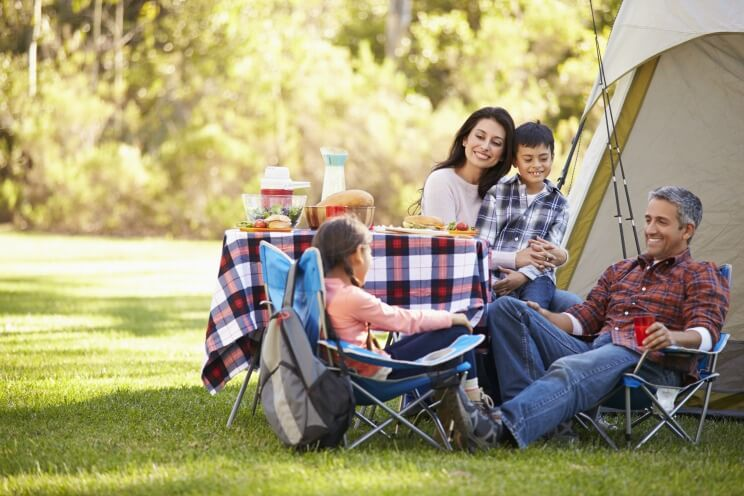 Family sat outside a tent enjoying their camping holiday