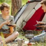 Two young campers cooking around a campfire
