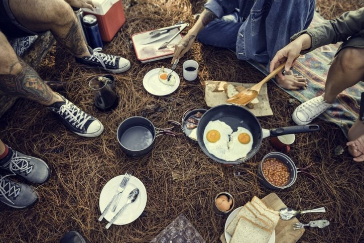 Group of friends cooking and eating at music festival