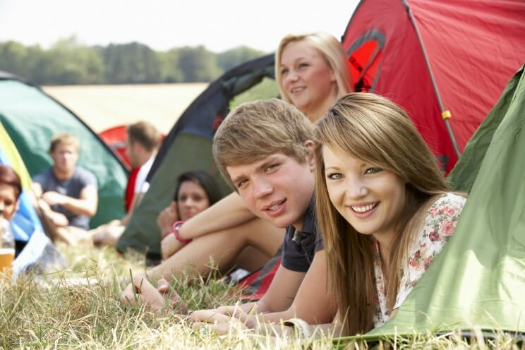 Young people camping at a music festival in their tents