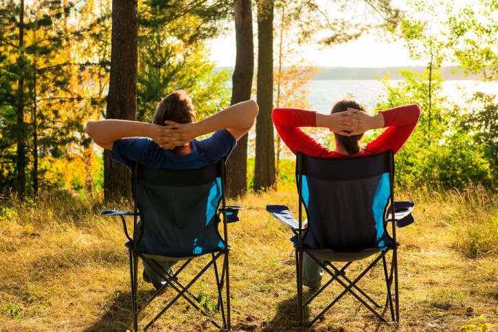 Two people relaxing on camping chairs