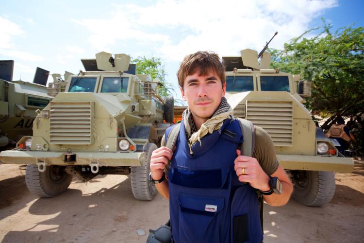 Adventurer Simon Reeve stood in front of military trucks
