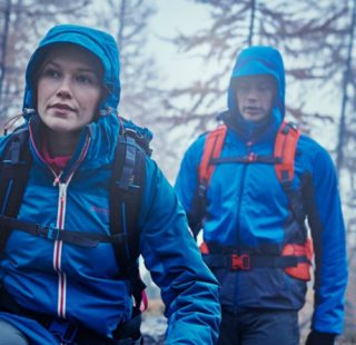 Man and woman walking in woods wearing waterproof jackets