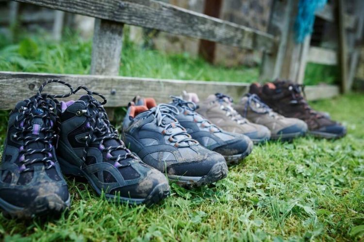 Several pairs of walking boots lined up against a fence
