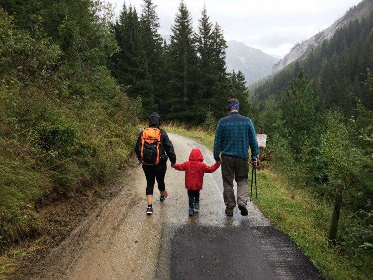 Family walking in the forest in the rain wearing waterproof clothing