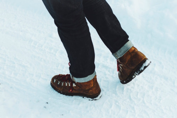Picture of someone's lower legs showing walking boots on snow