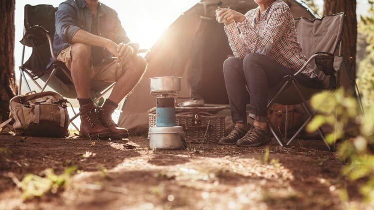 Two people camping with a camping stove