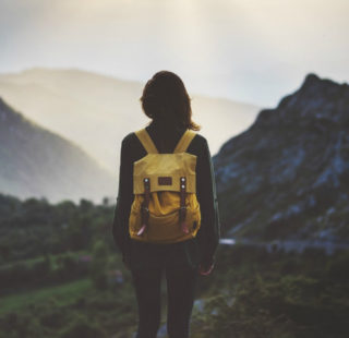 Woman standing on a mountain wearing a yellow rucksack