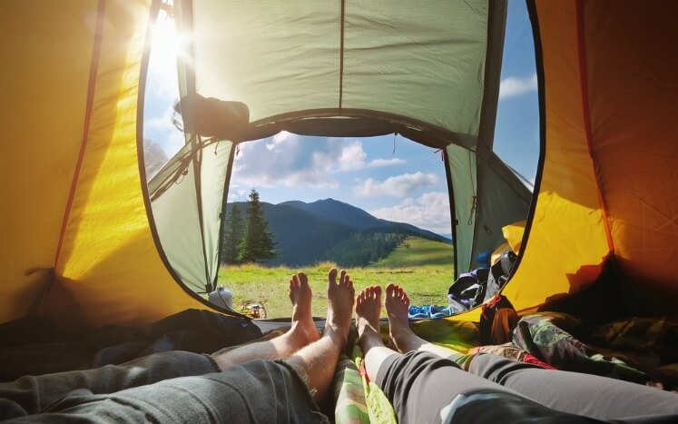 Two people lying in their tent with the door open in the sunshine