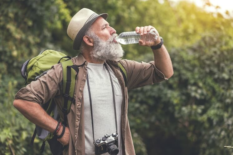 Old man drinking water when hiking