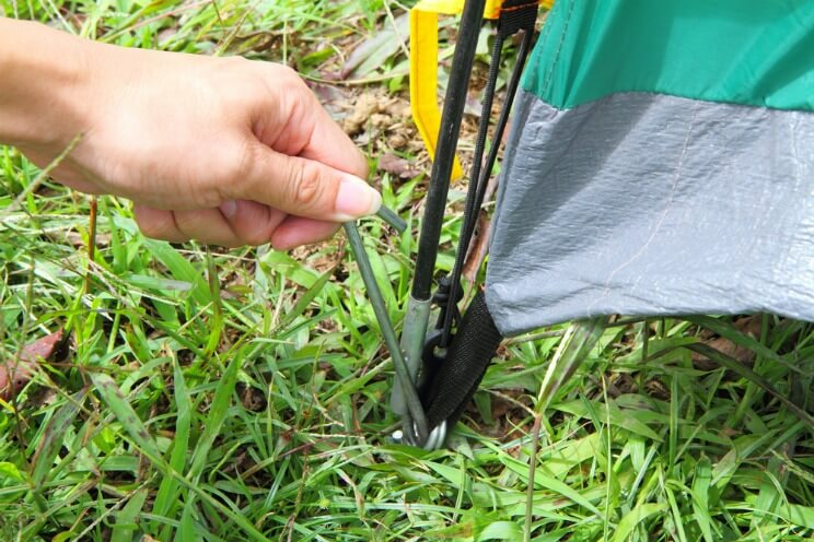 Person pegging down a tent with tent pegs