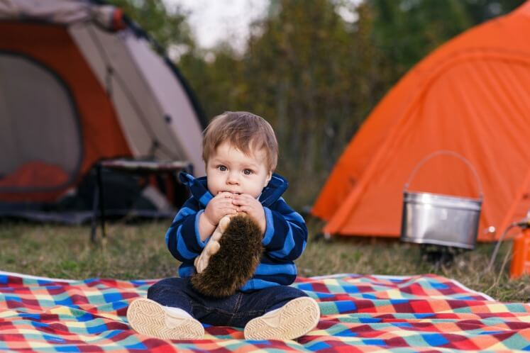 Baby camping sitting on a picnic rug