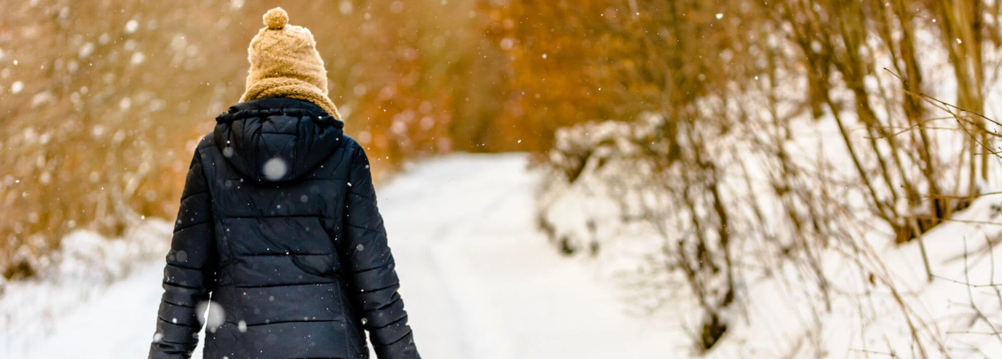 Woman in insulated coat walking through snow